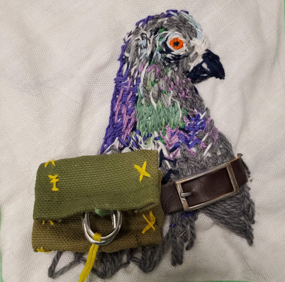 embroidery of a carrier pigeon with a back pack